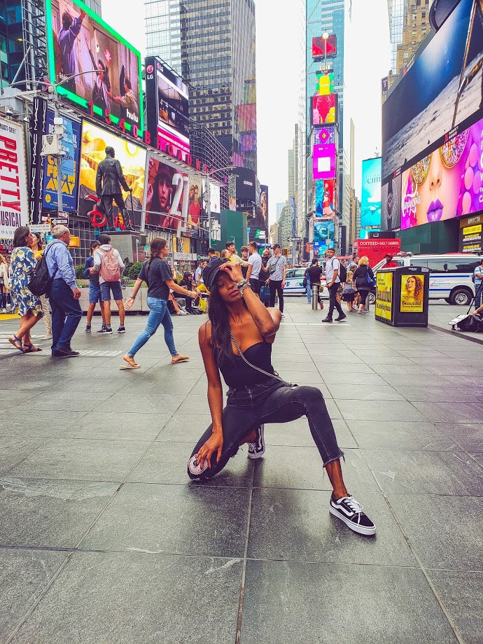 Woman kneeling in the middle of busy time square