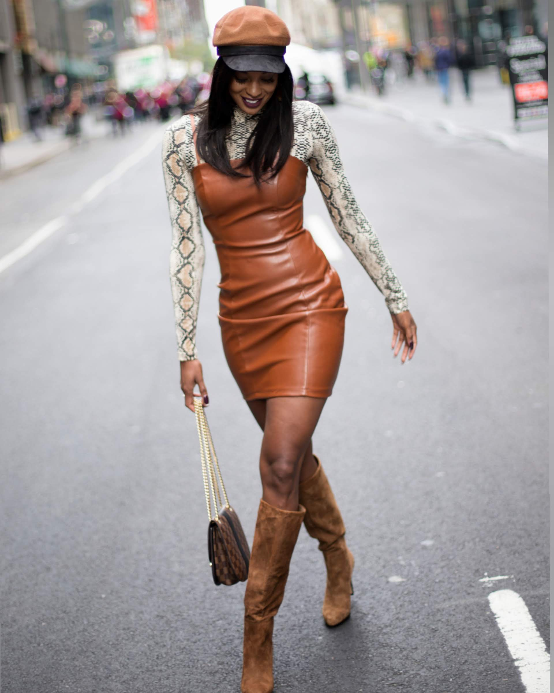 Girl wearing a brown dress, hat and knee high boots holding a purse in the middle of an NYC street