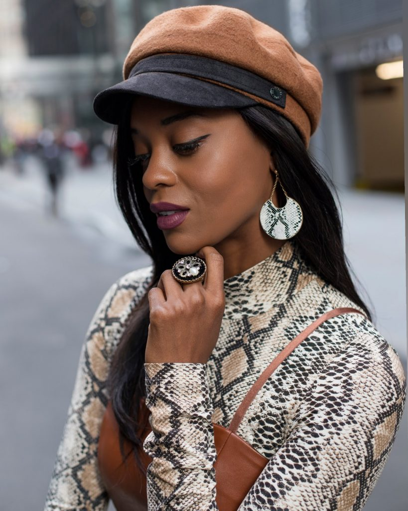 a close up of a woman in a brown hat, snake print top and snake print earrings