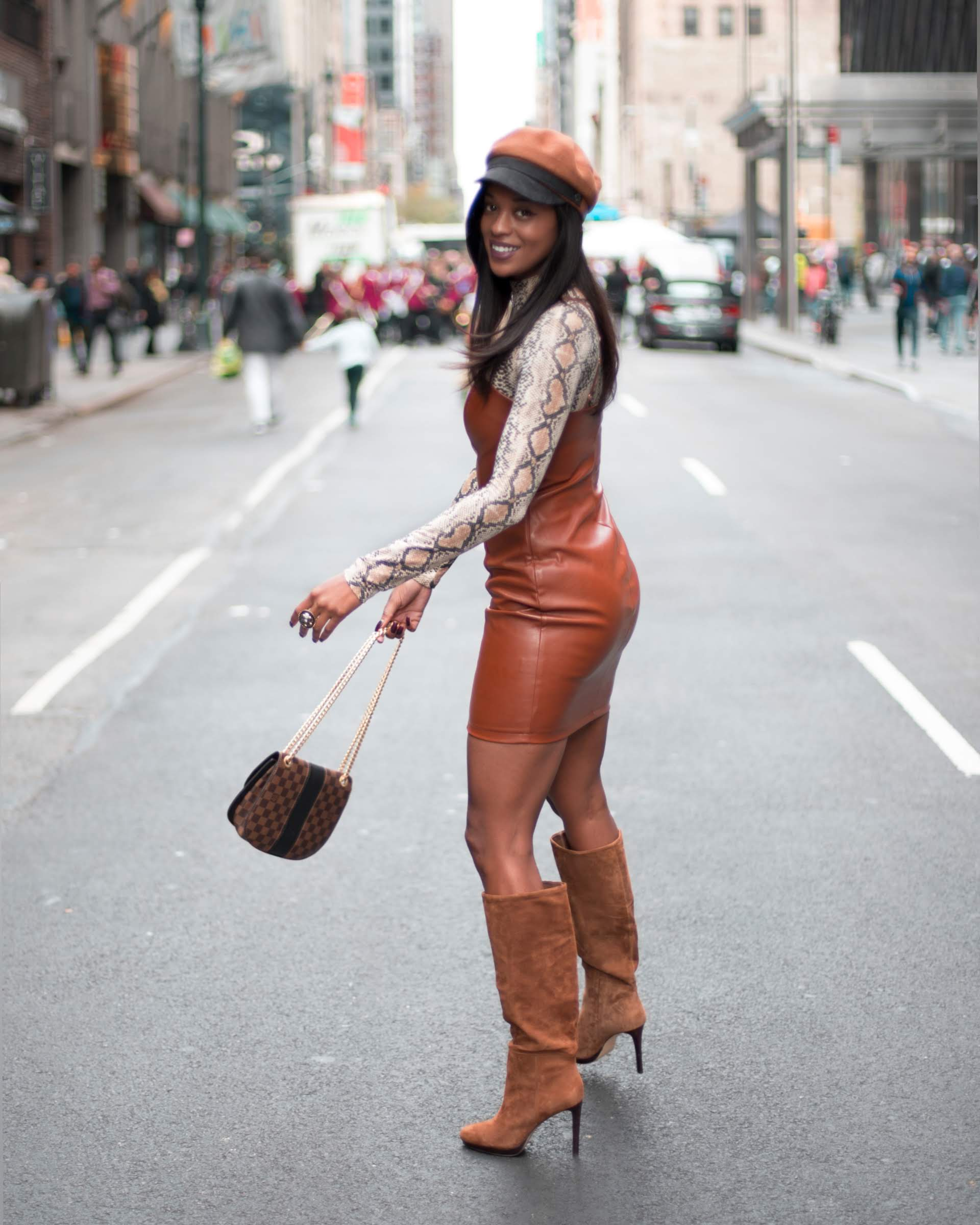 Girl standing in street holding a purse wearing brown knee high boots, brown leather dress and a snake print top