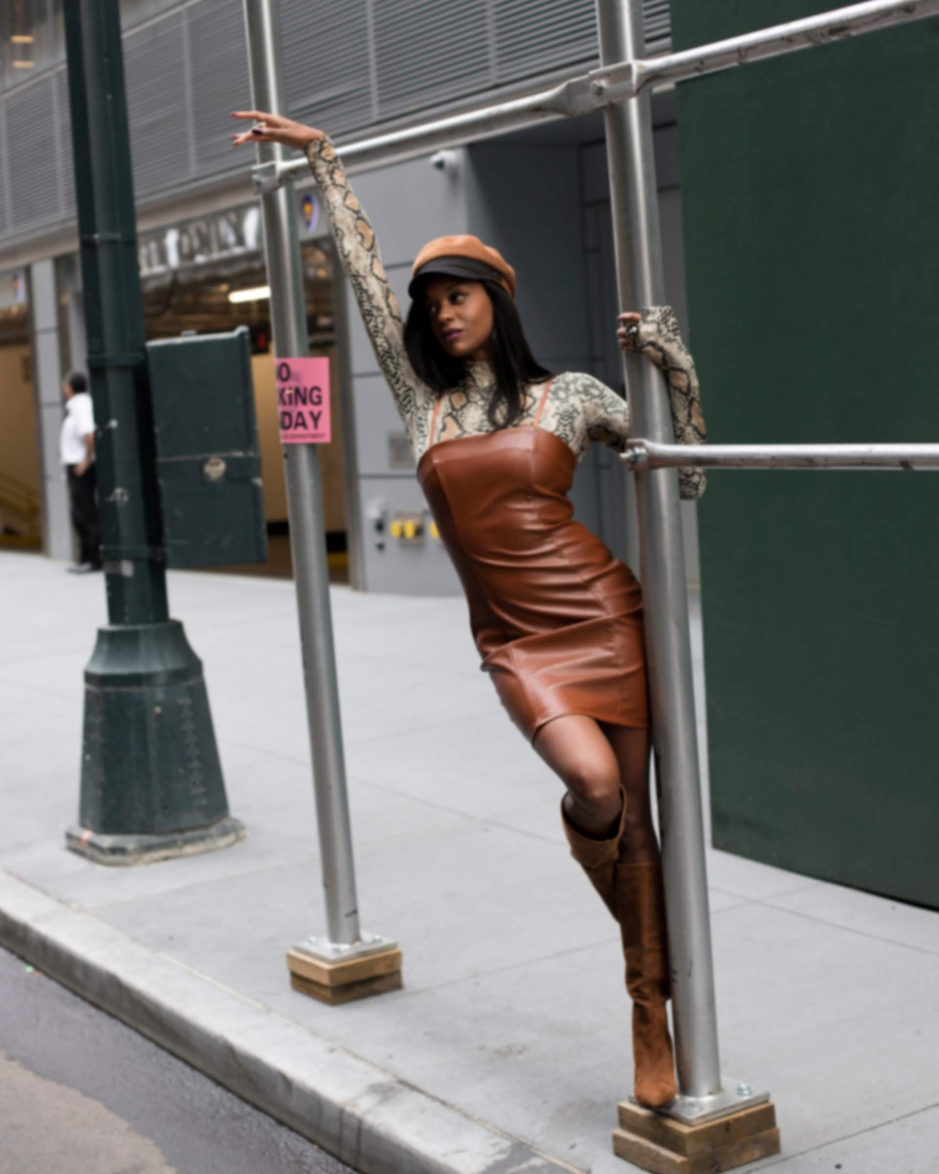 Girl wearing a brow hat, leather dress and boots with a snake print top holding a poll in NYC