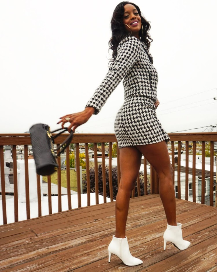 Woman in houndstooth moto jacket and mini skirt, white boots on a porch holding a bag