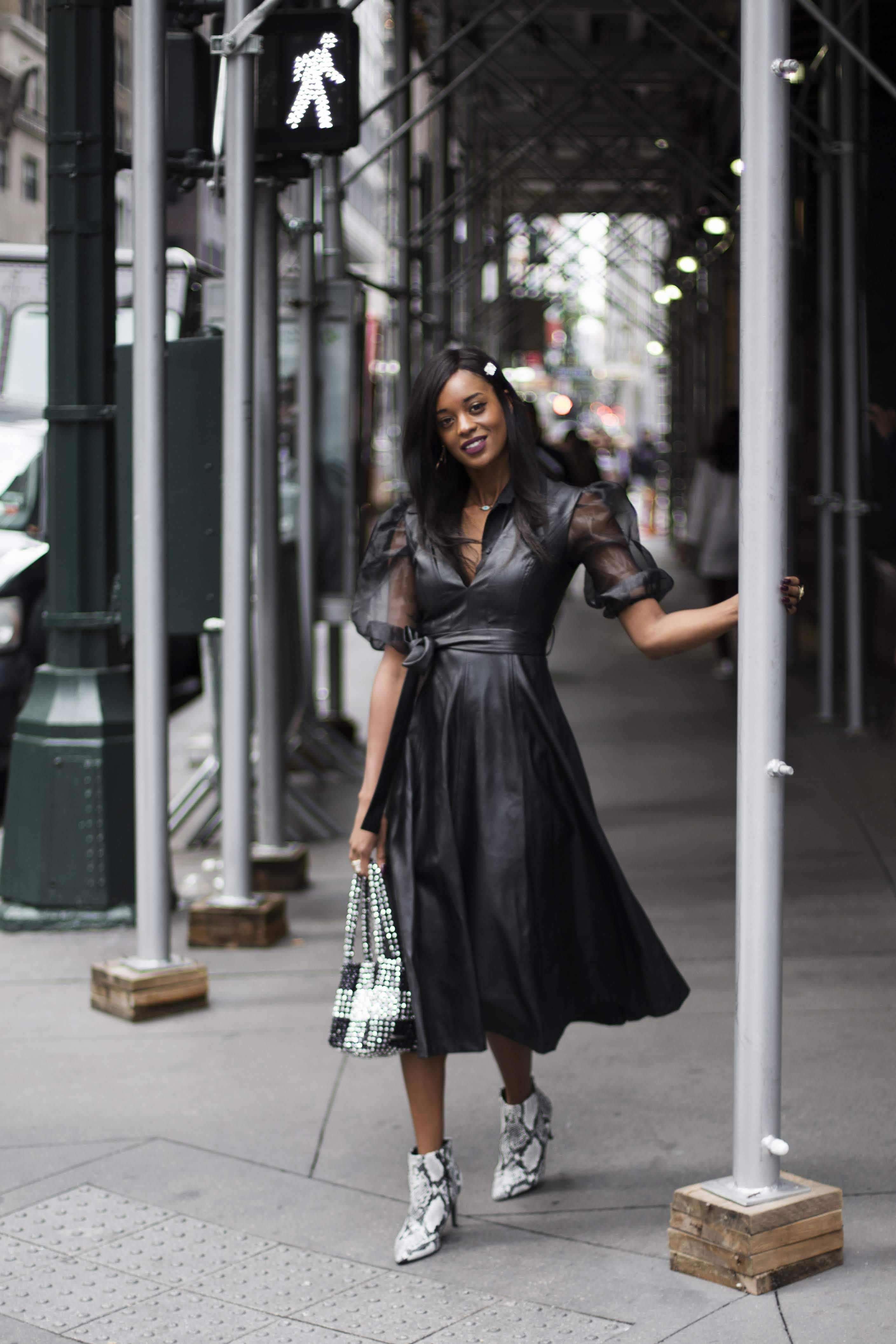Woman crossing a NYC street wearing a black leather dress and snake print shoes