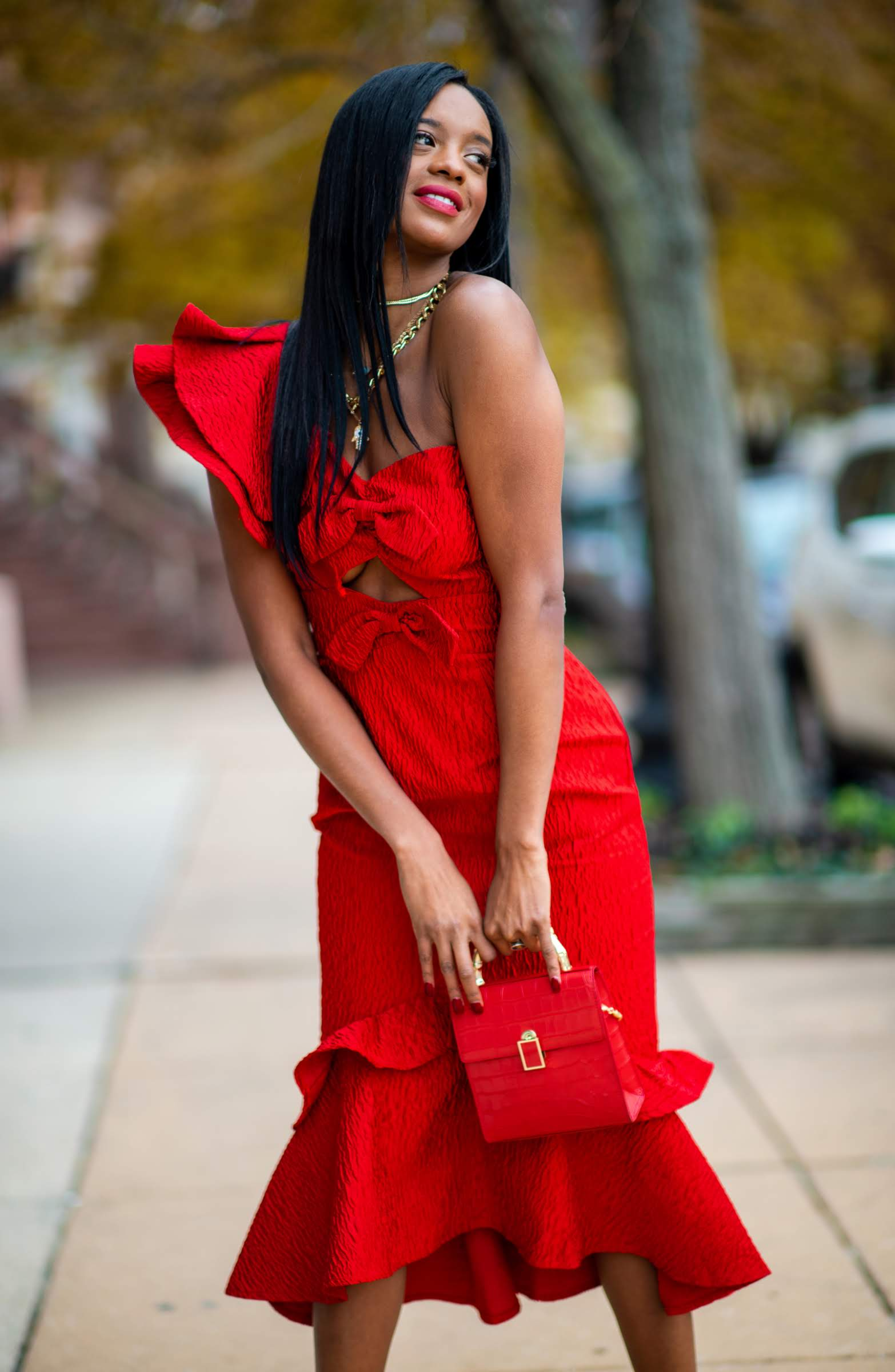 Valentine's Day Dress Code woman wearing midi length red dress and red purse outside and smiling