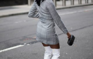 Woman walks down a NYC street wearing thigh highs and a blazer dress