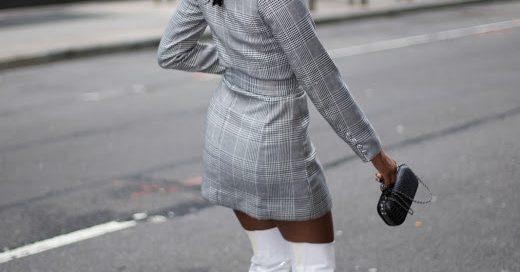 Woman walks down a NYC street wearing thigh highs and a blazer dress