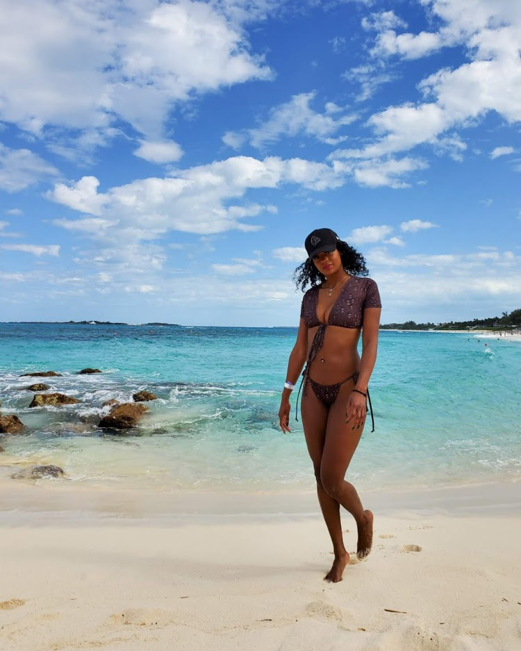 woman walks on tropical beach in a hat and bikini
