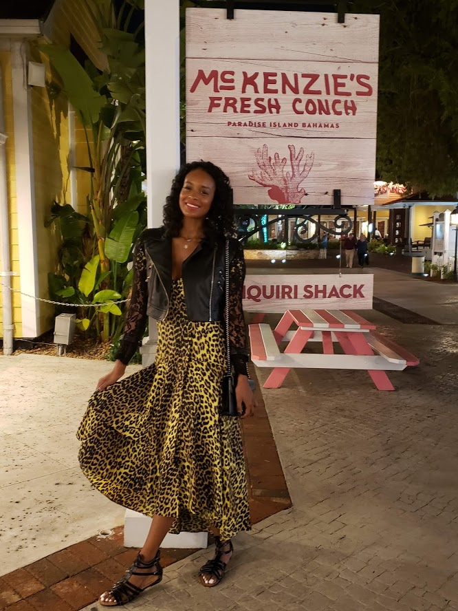 Girl wearing a yellow leopard maxi dress in front of a sign